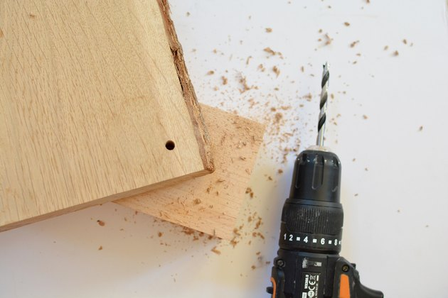 Power drill next to a piece of wood with a hole drilled through the corner