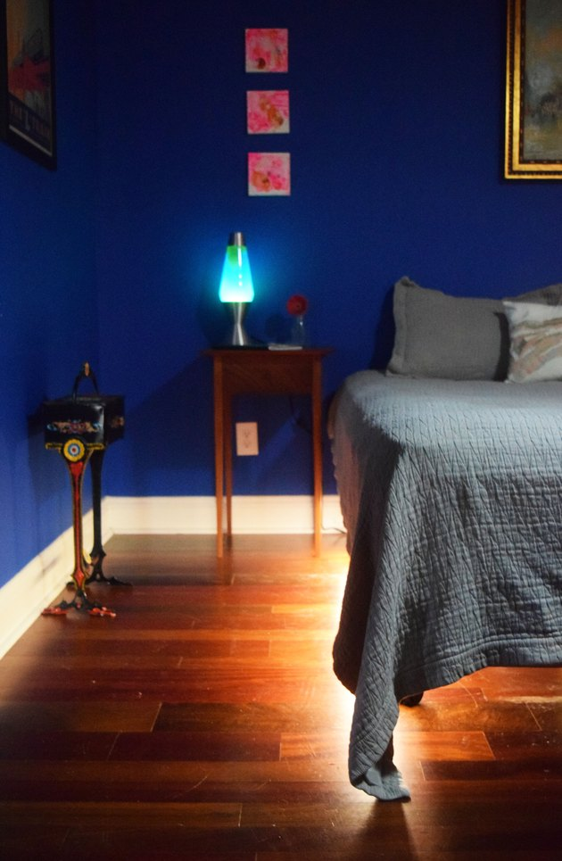 A bedroom corner with a lights emanating from under a bed on a hardwood floor. There is art on the walls, a small cast iron stand, and a wooden nightstand with a lava lamp on top.
