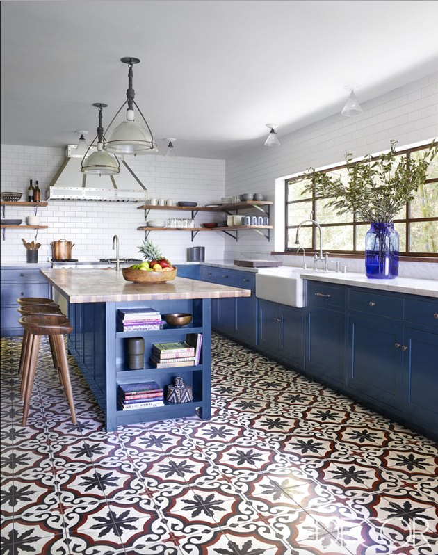 Moroccan kitchen floor tiles with blue cabinets and white countertops
