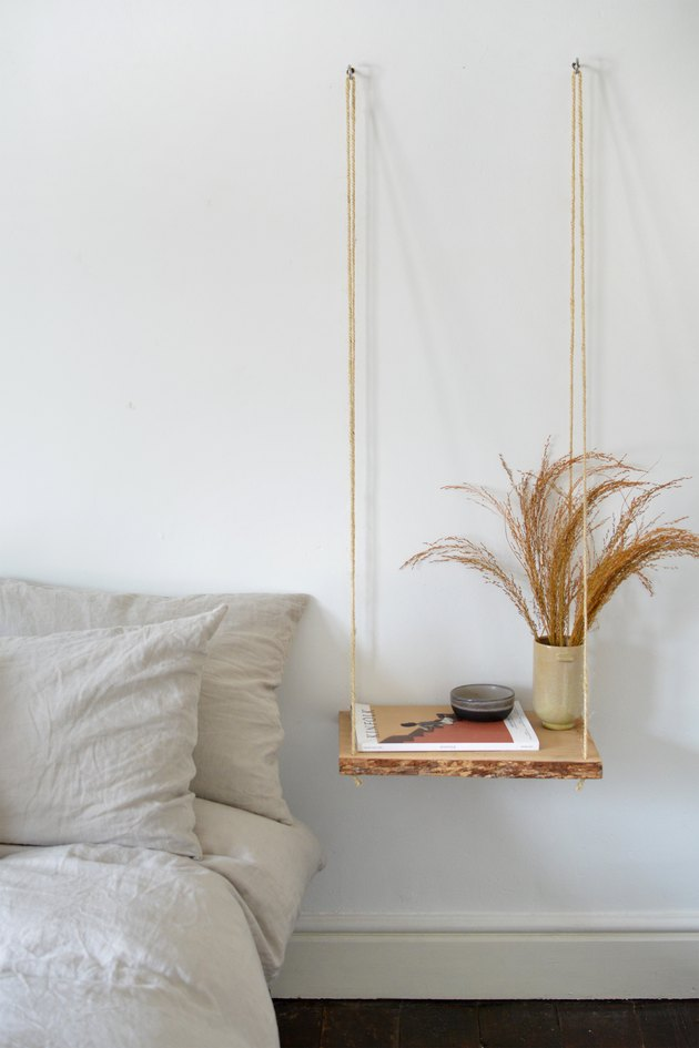 Wooden nightstand shelf with a vase of grasses hanging from two wall hooks next to a neutral bed and dark floor.