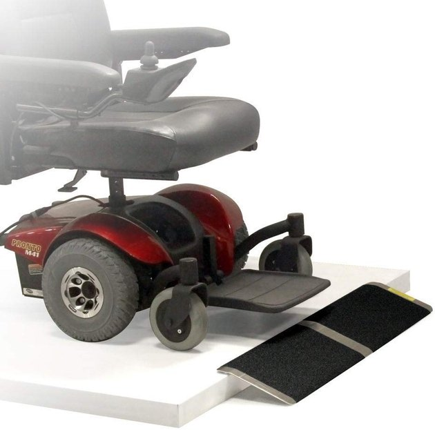 A red and black power wheelchair approaches a small black and aluminum ramp.