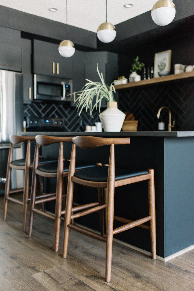 Black kitchen island with seating featuring wood stools and globe-style pendant lights