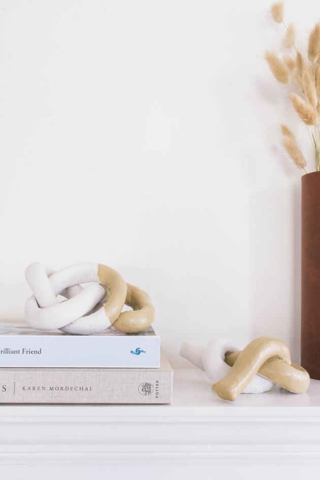 two diy clay knot sculptures on mantel with books