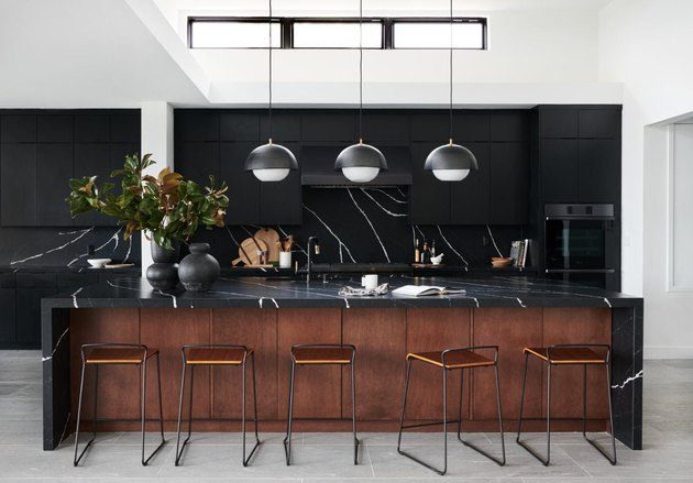 Black kitchen island with seating featuring black and white quartz and contemporary pendant lights