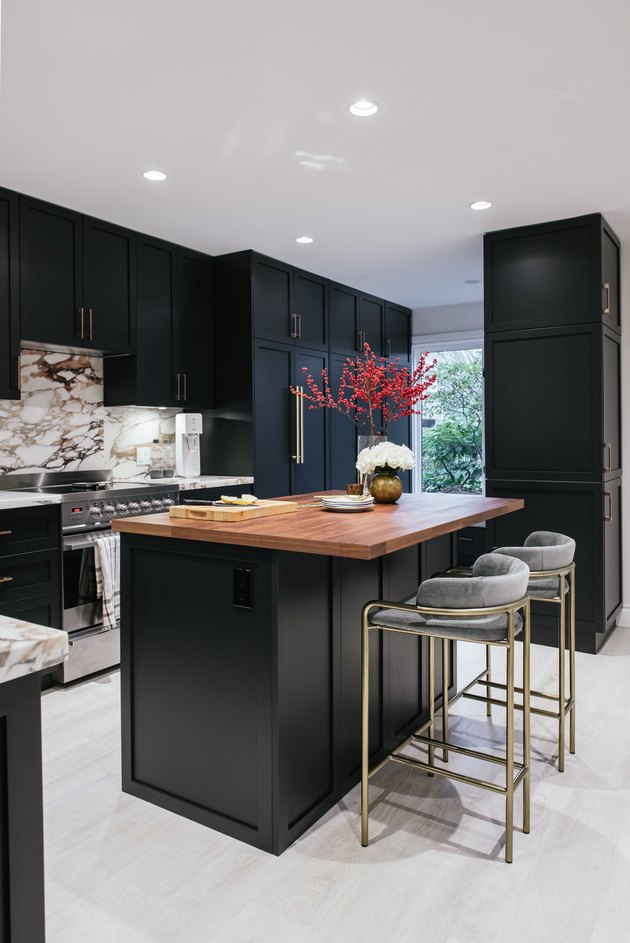 Black kitchen island with seating featuring brass bar stools and wood countertop