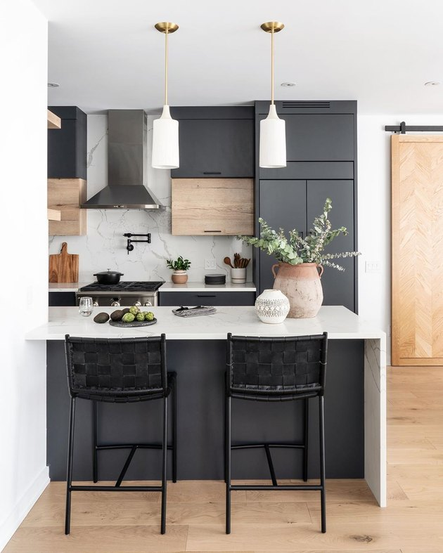 Black kitchen island with seating featuring white pendant lights and light wood finishes
