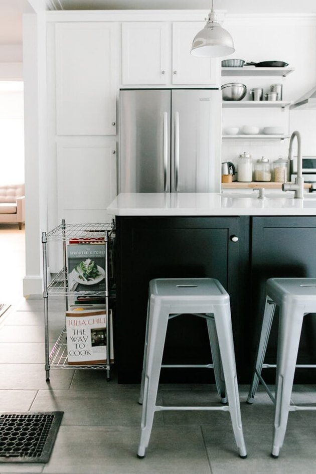 Black kitchen island with seating featuring featuring vintage metal chairs and white cabinets
