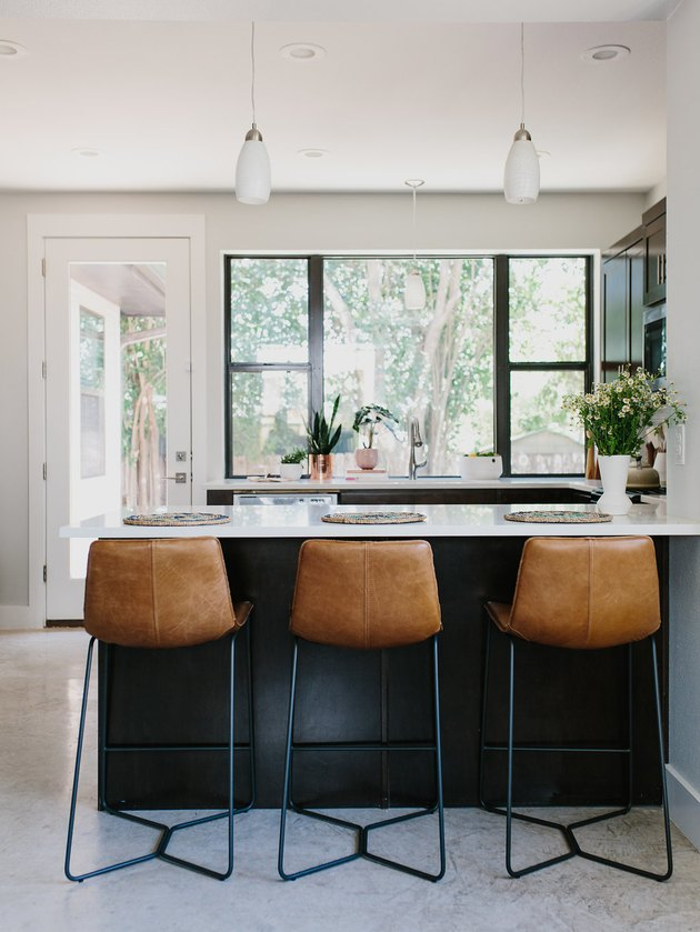 Black kitchen island with seating featuring leather bar stools and modern pendant lights