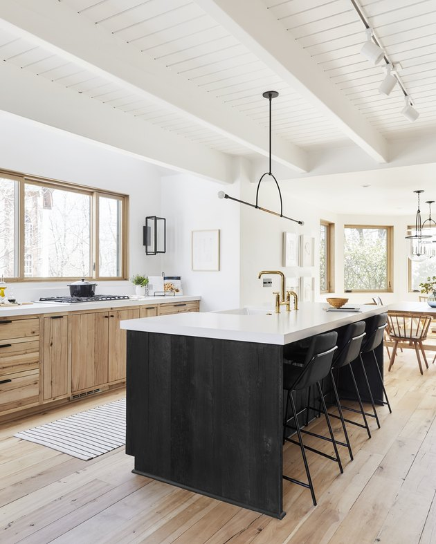 Black kitchen island with seating featuring featuring black chairs and a modern black chandelier