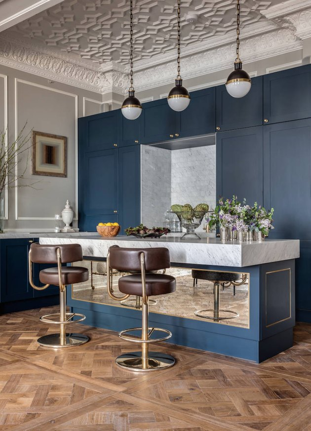 Inlaid wood floors, marble topped kitchen island, Art Deco stools and steel blue cabinets in a high ceiling kitchen.