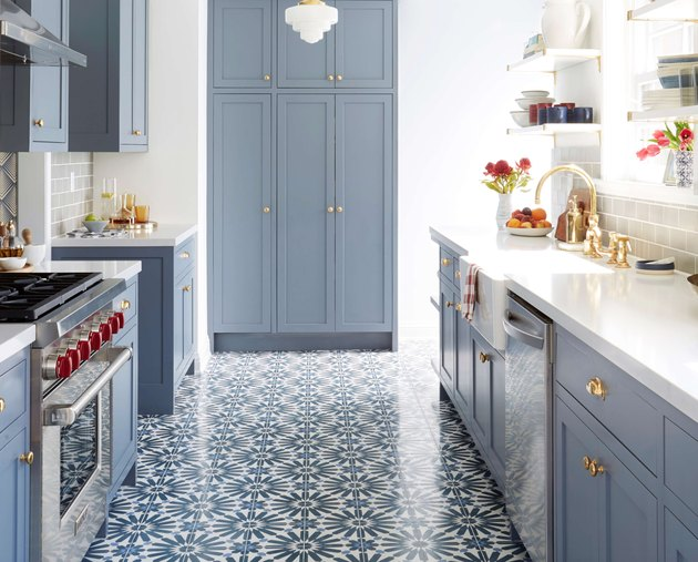 Blue patterned tile floor, blue cabinets, white counters and white pendant light.