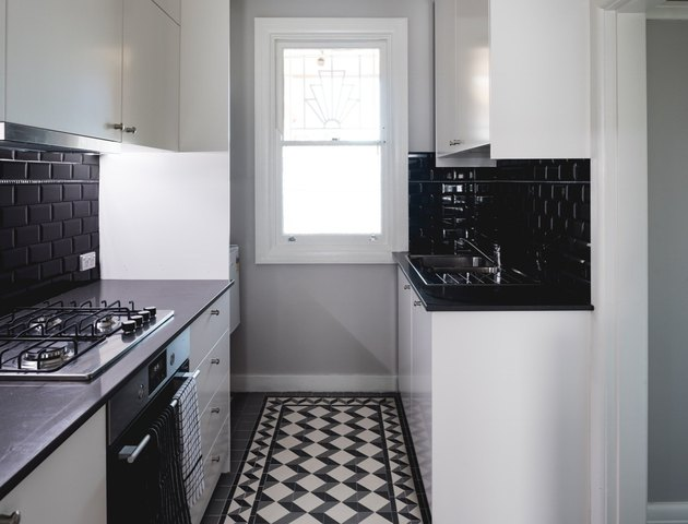 Black and white inlay tile, black tile backsplash, white cabinets.