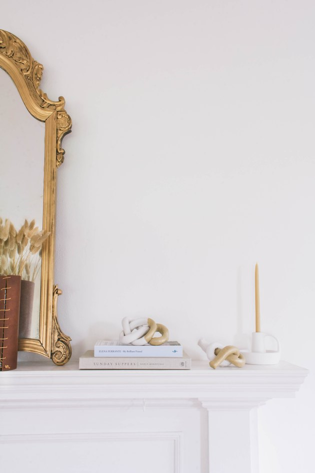 two diy clay knot sculptures on mantel with gold mirror, books and candle