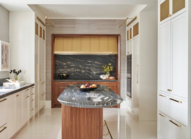 Oval kitchen island with marble counter, wooden base, white cabinets, glossy white flooring.