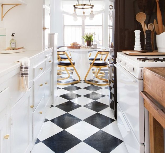 Black and white checkered floors, white cabinets and stove in vintage inspired kitchen with breakfast area.