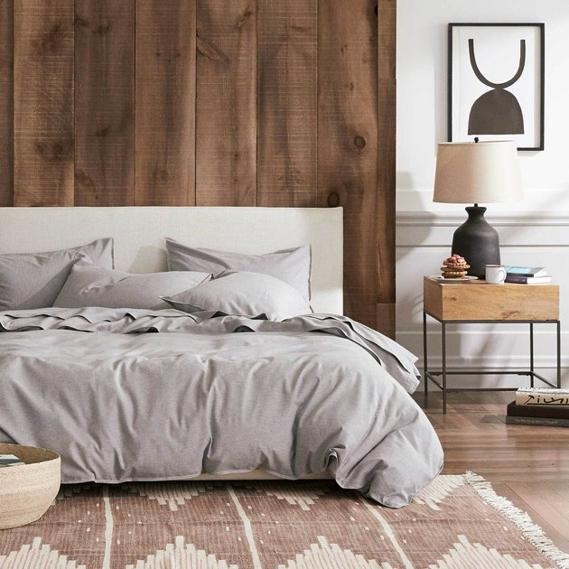 bedroom showing a bed with gray sheets and a wood backdrop with a side table and framed art print nearby