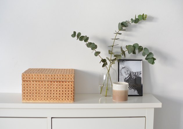 Cane box on white shelf with vase with eucalyptus