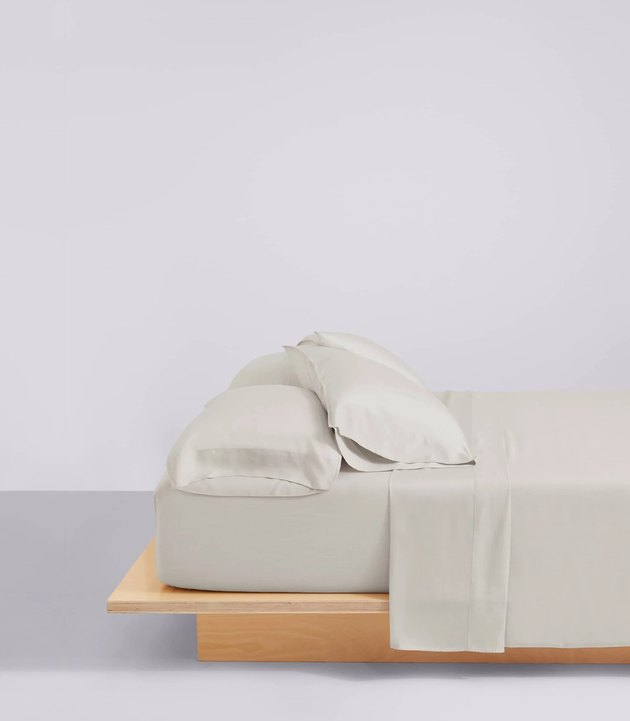 bed with wood frame and gray bedsheets