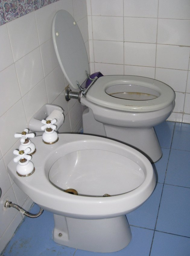 white toilet next to a white bidet in bathroom with blue and white tile