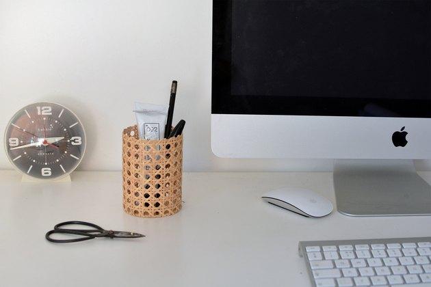 Pot de crayon de canne à côté de l'ordinateur, horloge, ciseaux et clavier en arrière-plan.
