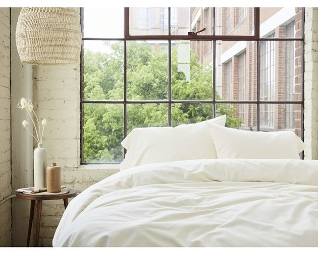 bedroom with small wood side table, woven lamp shade and bed with white sheets