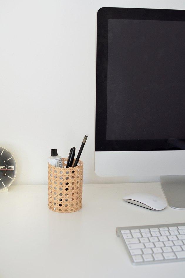 Pot de pensil de canne à côté de l'ordinateur et du clavier.