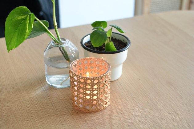 Bougeoir en rotin sur table en bois à côté d'un pot de fleurs et d'un vase en verre.