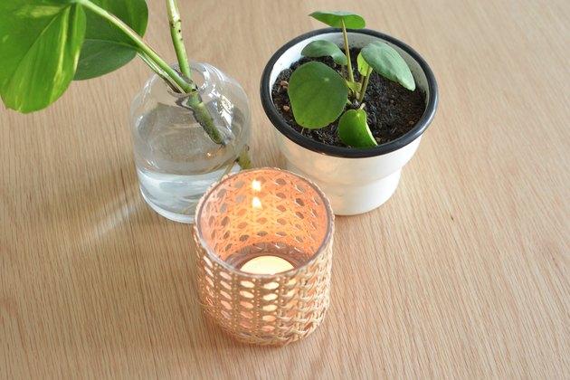 Bougeoir en canne avec bougie chauffe-plat allumée à l'intérieur. A côté d'un pot de fleurs et d'un vase en verre avec des plantes à l'intérieur.