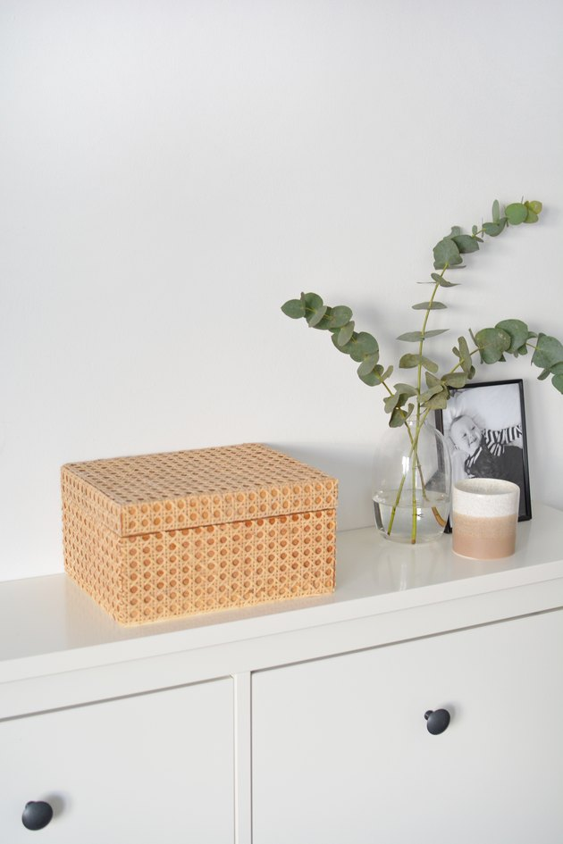 Wooden box covered in cabe on white unit with candle, framed photo and vase with greenery in background.