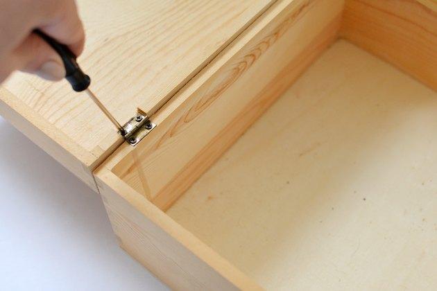 Boîte en bois ouverte avec tournevis retirant les charnières.