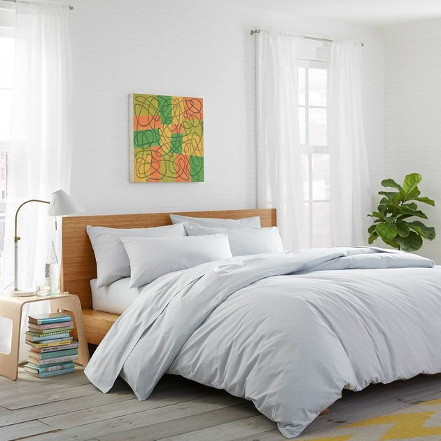 bedroom with side table with white lamp, bed with white sheets, and colorful artwork above the bed