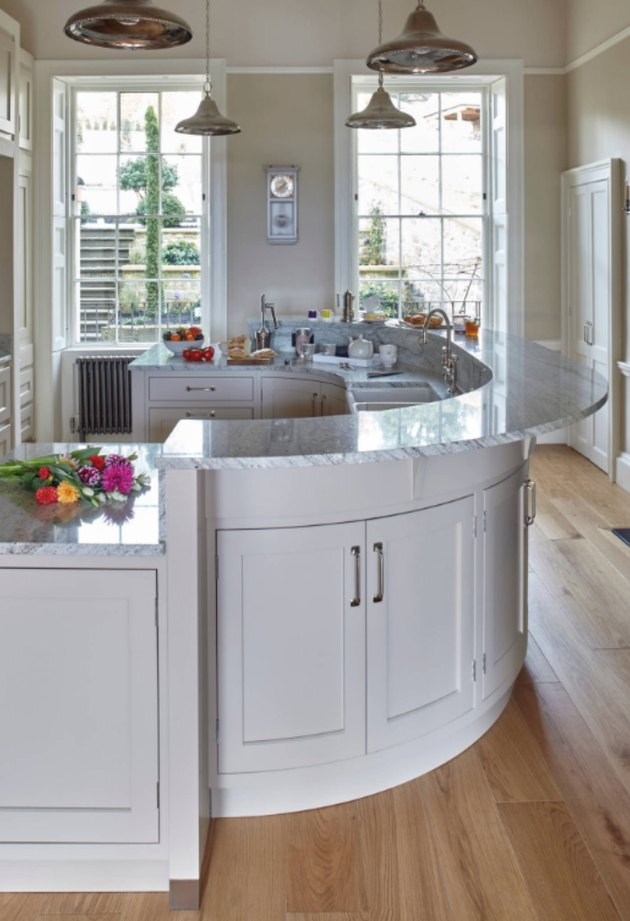 Half oval kitchen island with marble countertop and white cabinets.