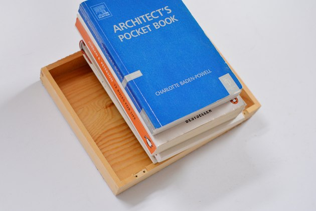 Stack of books weighing down on wooden box lid.