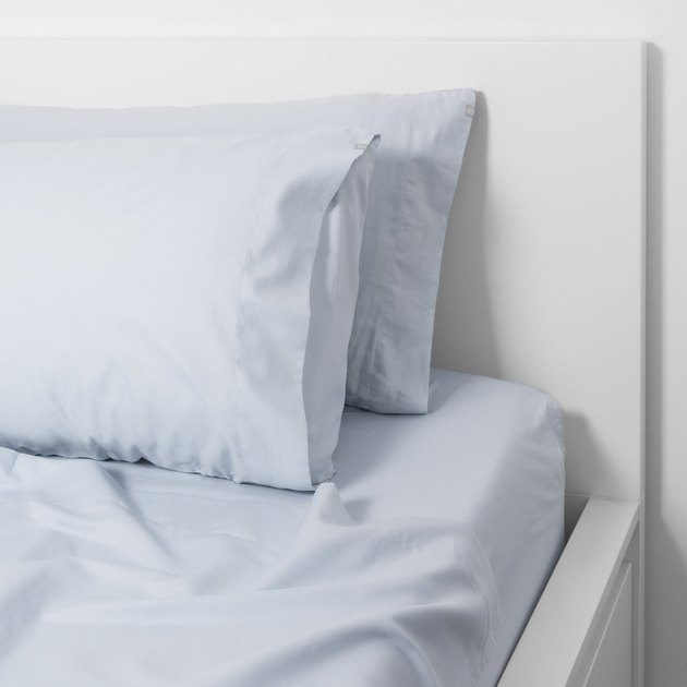 bed with white frame and blue sheets
