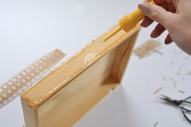 Hand applying glue to wooden box lid.