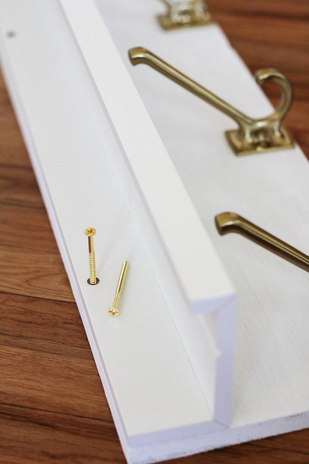 Vis en laiton longues utilisées pour fixer le panneau au mur