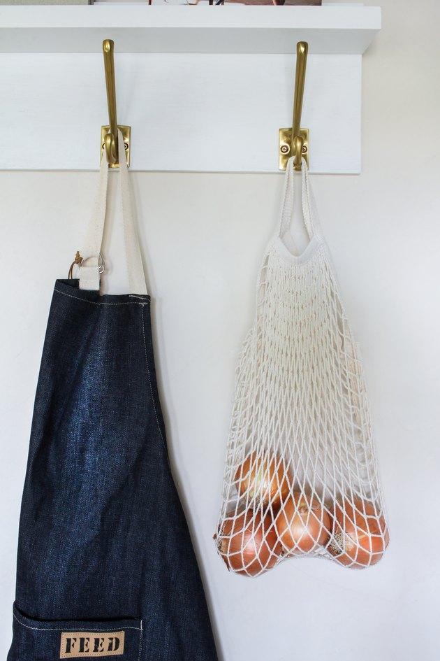 Tablier en jean et sac d'oignons suspendus à un organzier mural
