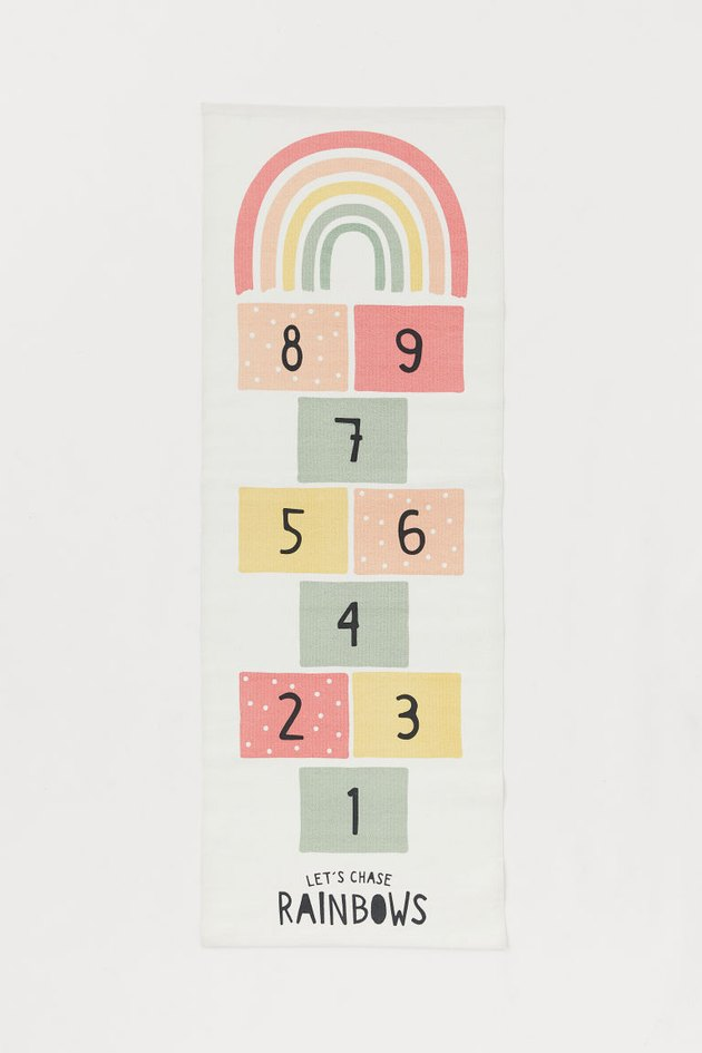 rug with hopscotch design in various colors and rainbow at the top, text at the bottom reads let's counts rainbows