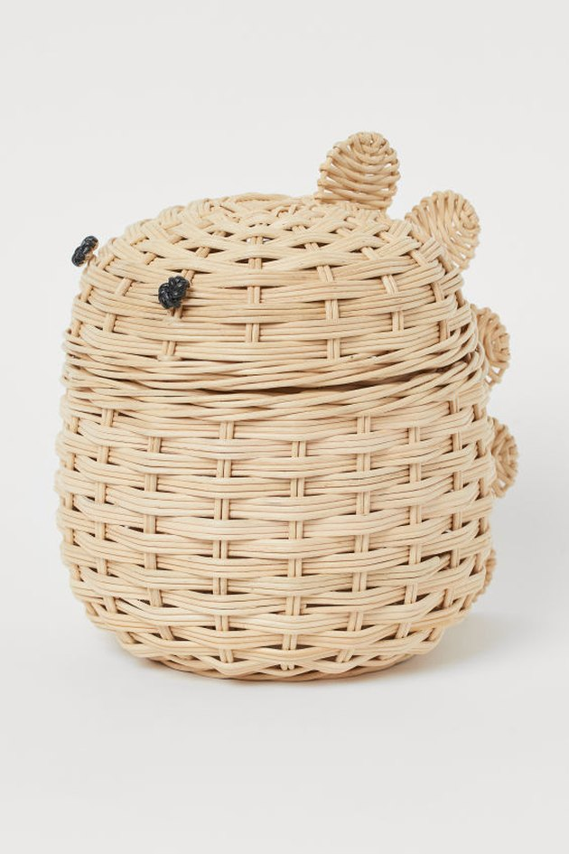 storage basket with two black dots for eyes and dinosaur scales on the back