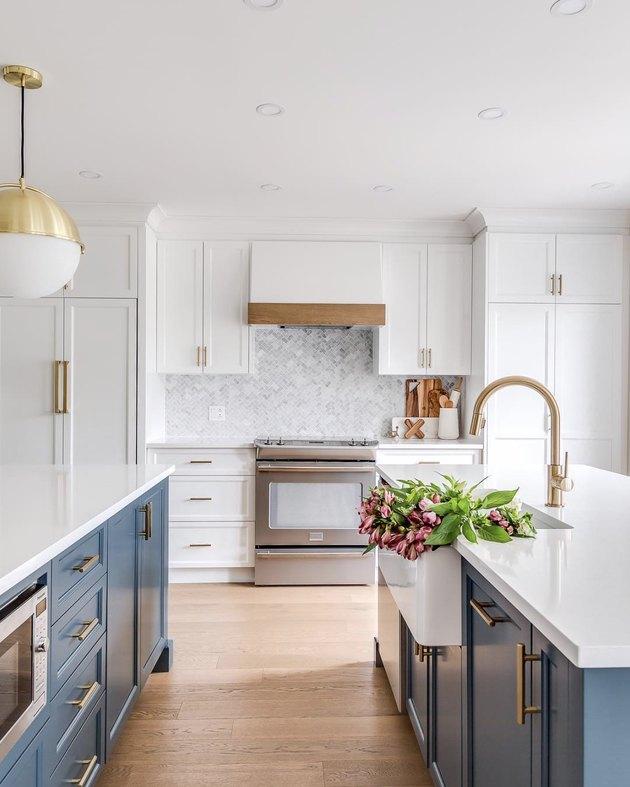 bright white kitchen with blue islands