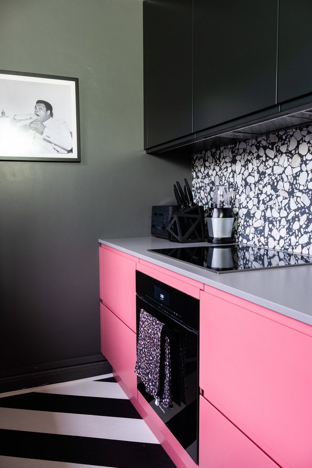 striped black and white kitchen floor with pink and black cabinets