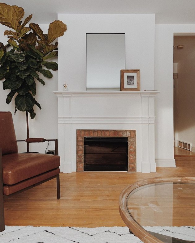 white Craftsman style fireplace with brick accent and white surround in living room