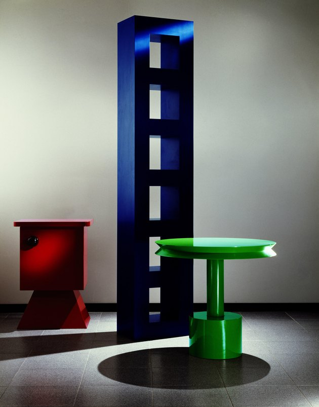 three pieces, one red short piece, tall blue piece, and green table, in Memphis Design style, designed by Aldo Cibic