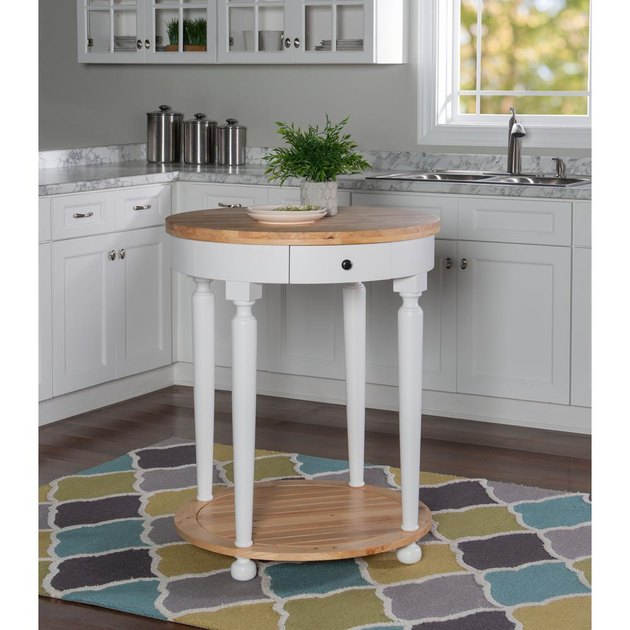 Small round kitchen island in white with wood countertop in white cabinet kitchen
