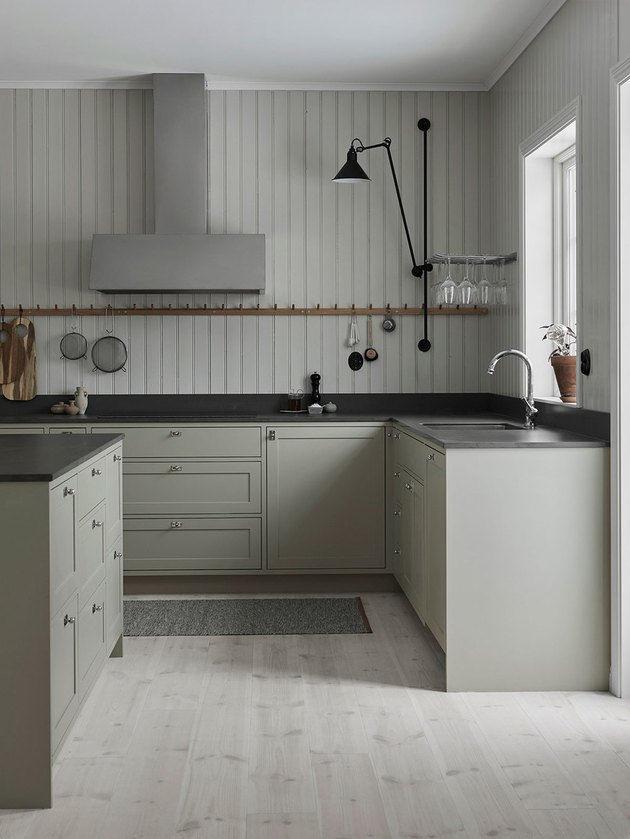 light wood kitchen floors with green cabinets by Nordiska Kok