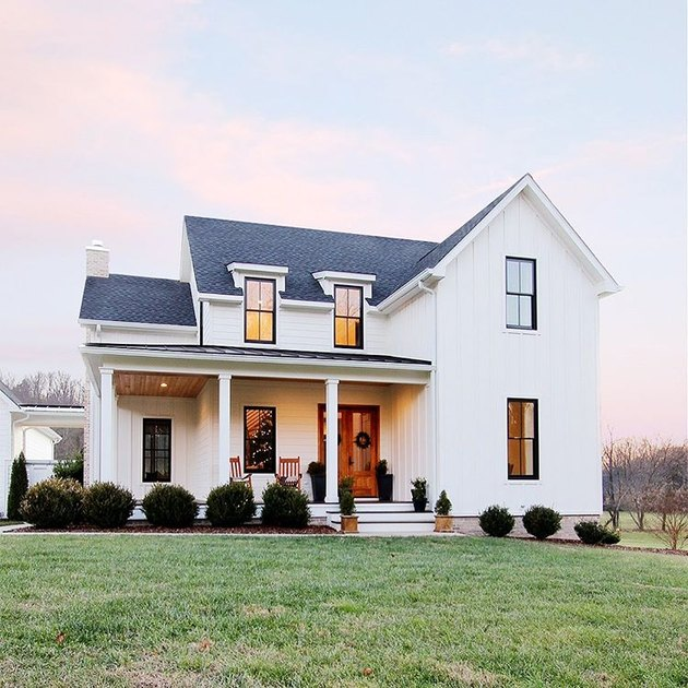 farmhouse style house with white rails and dark roof