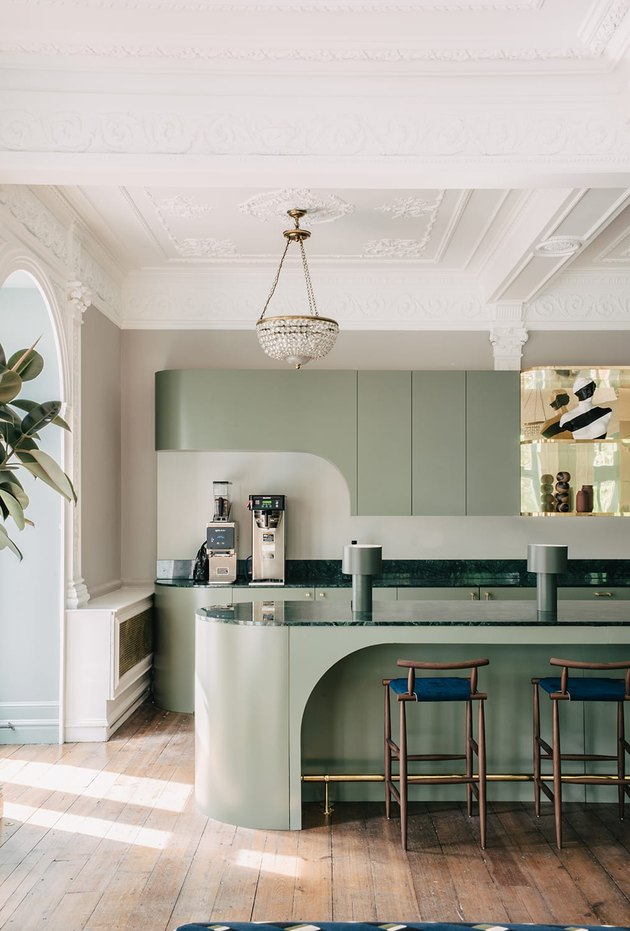Oval kitchen island in pastel green with bar chaialongside matching cabinets.