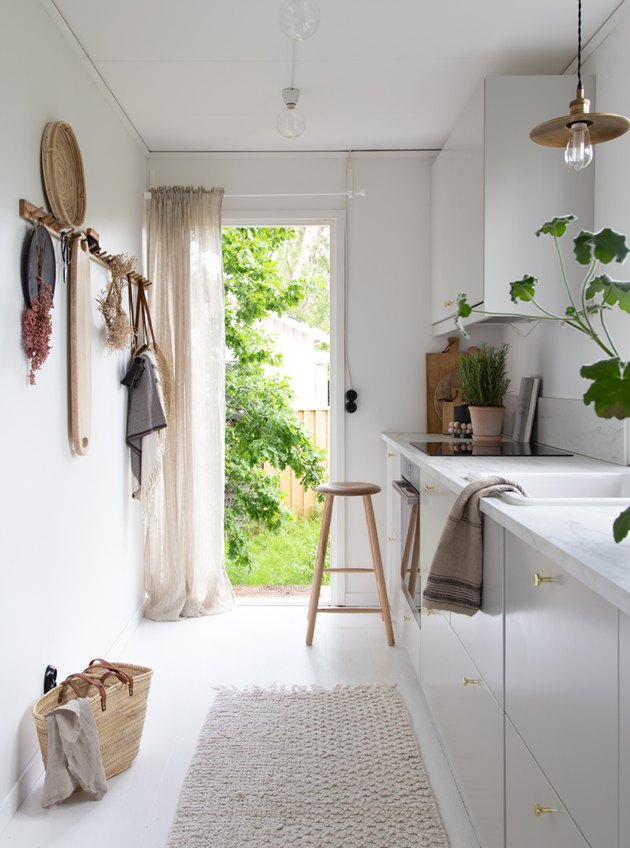 Scandinavian farmhouse kitchen with woven pieces and white cabinets