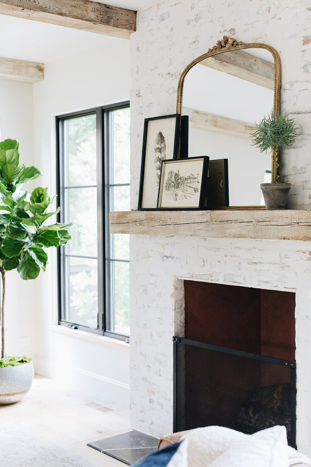 wood mantel with white washed brick fireplace