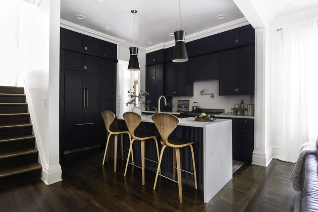 Dark wood kitchen flooring idea with modern bar stools and black cabinets